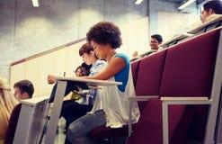 Grupo de estudiantes con los cuadernos en la sala de conferencias imágenes de archivo libres de regalías