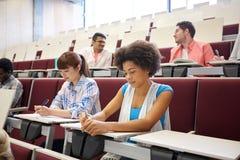 Grupo de estudiantes con los cuadernos en la sala de conferencias Foto de archivo libre de regalías