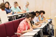 Grupo de estudiantes con los cuadernos en sala de conferencias Fotos de archivo