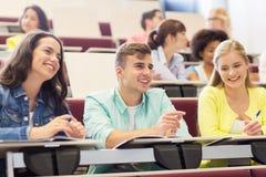 Grupo de estudiantes con los cuadernos en sala de conferencias Foto de archivo libre de regalías