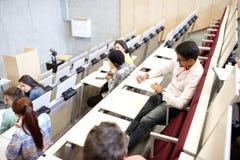 Grupo de estudiantes con los cuadernos en sala de conferencias Imágenes de archivo libres de regalías