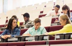 Grupo de estudiantes con los cuadernos en sala de conferencias Fotografía de archivo libre de regalías