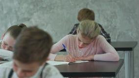 Grupo de estudiantes con los cuadernos que escriben la prueba en la escuela almacen de metraje de vídeo
