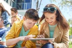 Grupo de estudiantes con PC de la tableta en el patio de escuela Fotos de archivo libres de regalías