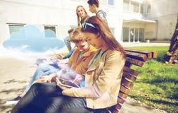 Grupo de estudiantes con PC de la tableta en el patio de escuela Imagenes de archivo