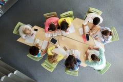 Grupo de estudiantes con PC de la tableta en la biblioteca escolar Foto de archivo