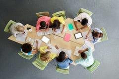 Grupo de estudiantes con PC de la tableta en la biblioteca escolar Imagen de archivo