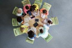 Grupo de estudiantes con PC de la tableta en la biblioteca escolar Foto de archivo libre de regalías