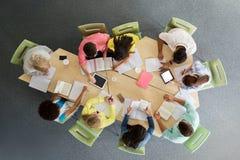 Grupo de estudiantes con PC de la tableta en la biblioteca escolar Imágenes de archivo libres de regalías