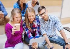Grupo de estudiantes con PC de la tableta y la taza de café Imagen de archivo