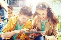 Grupo de estudiantes con PC de la tableta en el patio de escuela Fotos de archivo