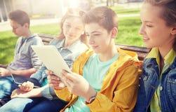 Grupo de estudiantes con PC de la tableta en el patio de escuela Imagen de archivo libre de regalías