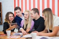 Grupo de estudiantes creativos jovenes de los empresarios con la tableta digital Foto de archivo libre de regalías