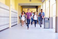 Grupo de estudiantes de la High School secundaria que corren en pasillo Foto de archivo