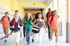 Grupo de estudiantes de la High School secundaria que corren a lo largo del pasillo