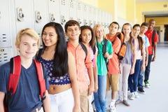Grupo de estudiantes de la High School secundaria que se colocan en pasillo Fotos de archivo libres de regalías
