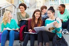 Grupo de estudiantes de la High School secundaria que se sientan fuera del edificio Imagenes de archivo