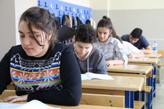 Grupo de estudiantes de la High School secundaria que toman una prueba en sala de clase Foto de archivo libre de regalías