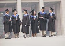 Grupo de estudiantes de tercer ciclo en vestidos de la graduación y de birretes que se colocan y que hablan con los diplomas en ma Foto de archivo libre de regalías