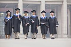 Grupo de estudiantes de tercer ciclo sonrientes en vestidos de la graduación y de birretes que colocan los diplomas en manos Foto de archivo