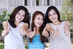 Grupo de estudiantes del adolescente con los pulgares para arriba Foto de archivo