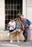 Grupo de estudiantes delante de la universidad con el teléfono elegante Imagen de archivo libre de regalías