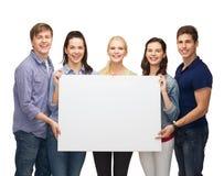 Grupo de estudiantes derechos con el tablero blanco en blanco Imágenes de archivo libres de regalías