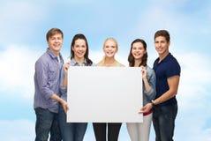 Grupo de estudiantes derechos con el tablero blanco en blanco Imagen de archivo libre de regalías