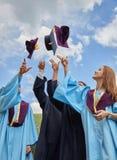 Grupo de estudiantes en vestidos y casquillos de la graduación Imagenes de archivo
