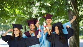 Grupo de estudiantes en vestidos y casquillos de la graduación Fotos de archivo