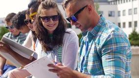 Grupo de estudiantes felices con los cuadernos en el campus metrajes