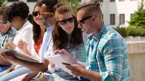 Grupo de estudiantes felices con los cuadernos en el campus almacen de video