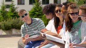 Grupo de estudiantes felices con los cuadernos en el campus almacen de metraje de vídeo
