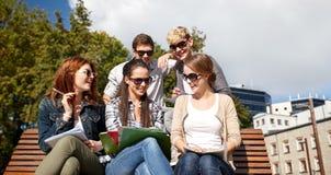 Grupo de estudiantes felices con los cuadernos en el campus Foto de archivo libre de regalías