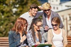 Grupo de estudiantes felices con los cuadernos en el campus Fotografía de archivo