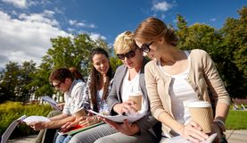 Grupo de estudiantes felices con los cuadernos y el café Imagenes de archivo