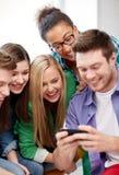 Grupo de estudiantes felices con smartphone en la escuela Fotografía de archivo libre de regalías