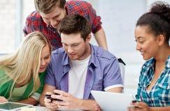 Grupo de estudiantes felices con smartphone en la escuela Imágenes de archivo libres de regalías