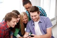 Grupo de estudiantes felices con smartphone en la escuela Imagen de archivo
