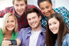 Grupo de estudiantes felices con smartphone en la escuela Foto de archivo libre de regalías