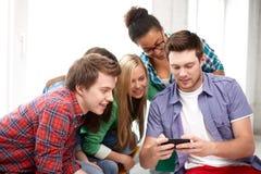 Grupo de estudiantes felices con smartphone en la escuela Fotos de archivo libres de regalías