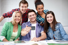 Grupo de estudiantes felices con smartphone en la escuela Fotografía de archivo