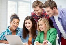 Grupo de estudiantes felices de la High School secundaria con el ordenador portátil Imagenes de archivo