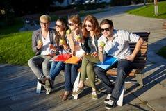 Grupo de estudiantes felices que comen manzanas verdes Foto de archivo libre de regalías