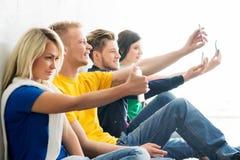 Grupo de estudiantes felices que están en una rotura que toma el selfie Imagenes de archivo