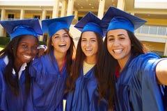 Grupo de estudiantes femeninos de la High School secundaria que celebran la graduación Imagen de archivo