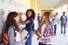 Grupo de estudiantes femeninos de la High School secundaria que hablan por los armarios Imágenes de archivo libres de regalías