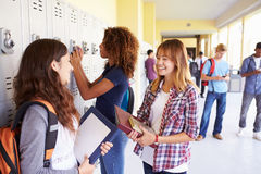 Grupo de estudiantes femeninos de la High School secundaria que hablan por los armarios imagenes de archivo