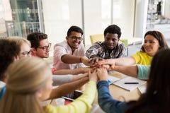 Grupo de estudiantes internacionales con las manos en el top Imagenes de archivo