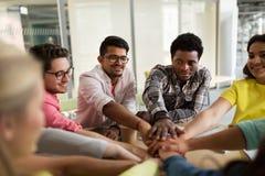 Grupo de estudiantes internacionales con las manos en el top Imágenes de archivo libres de regalías